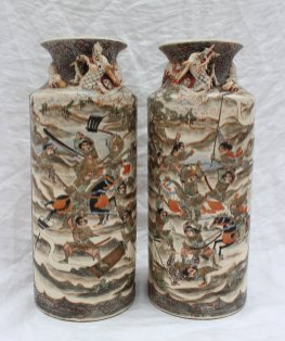 22nd August - Asian Ceramics Lot 304. A pair of Japanese Satsuma pottery vases, of cylindrical form with a flared neck, applied with a dragon to the neck, the body painted with panels of samurai and deities, script and seal mark to the base, 31cm high