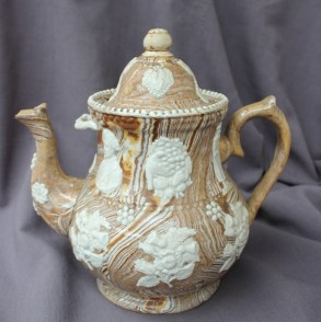Lot 335A - Of Earl Grey interest: A large early 19th century agate ware type pottery teapot, the slip glaze with mouldings possibly depicting Charles Grey, 2nd Earl Grey, a Chinese man, tea leaves, bergamots (a main ingredient of Earl Grey tea), and motifs of flowers 30cm high