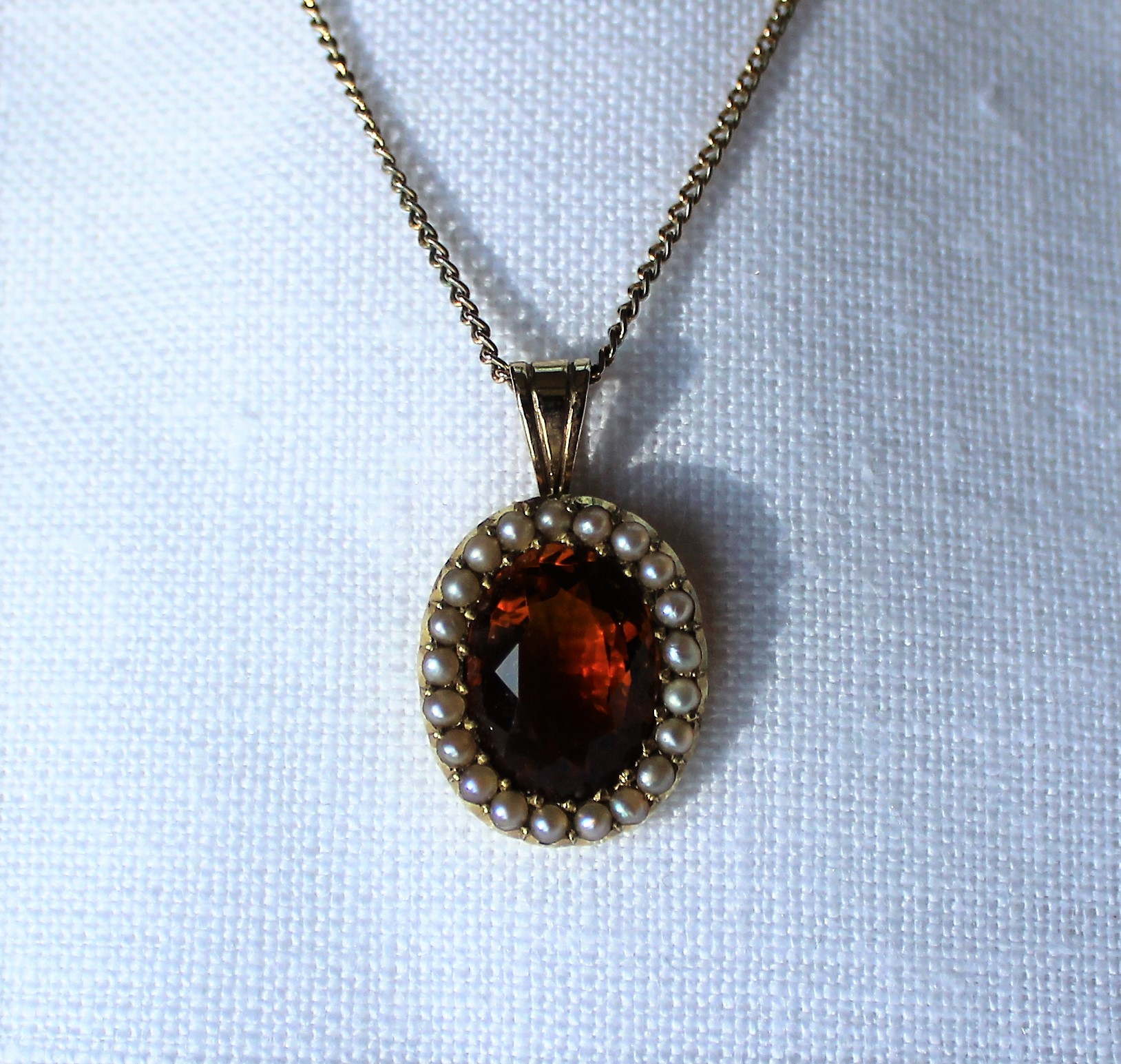 Lot 29 - Estimates: £70 - 90 - A 15ct gold citrine and seed pearl pendant set with an oval faceted citrine surrounded by seed pearls on a gold plated chain