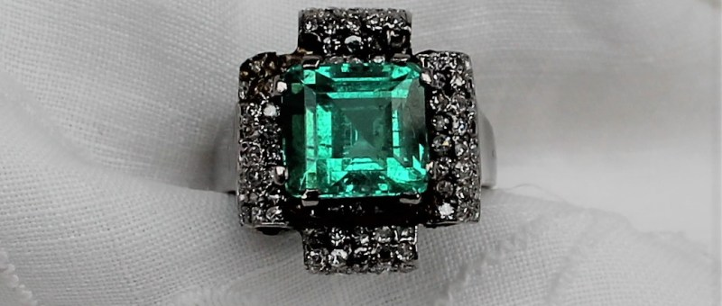 Lot 100 - Estimate £4,000 - 6,000, An Emerald and diamond ring, the central square cut emerald approximately 9mm x 9mm estimated at 4cts, surrounded by rould old brilliant cut diamonds to a white metal setting and shank, size p, overall approximately 7.5 grams