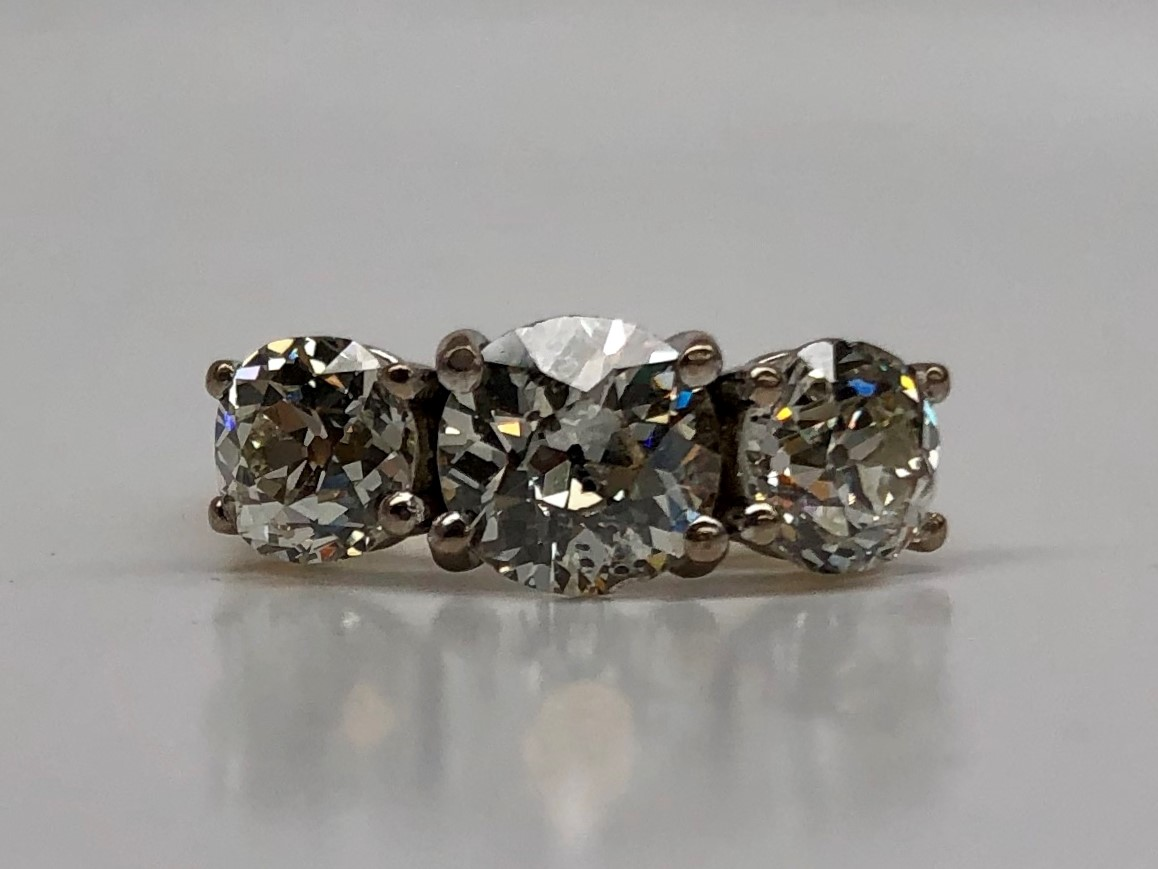 Lot 24 - Estimate £2,000 - 2,500, A three stone diamond ring, set with old round cut diamonds, the centre stone approximately 1.25cts, flanked by two diamonds, each approximately 0.75cts to a white metal setting and shank, size approximately H 1/2, overall approximately 4.2 grams