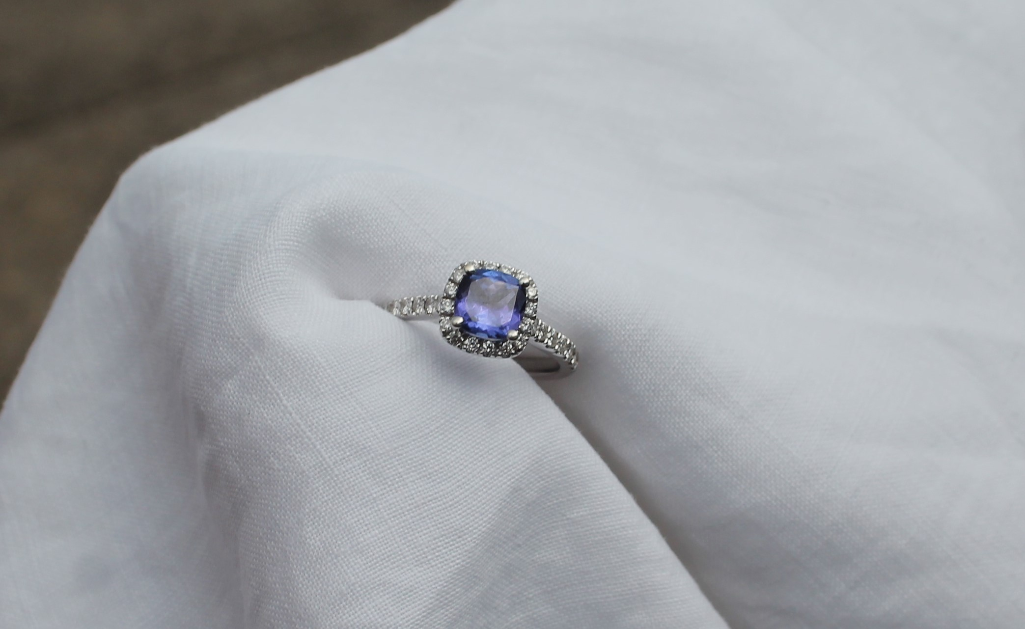 Lot 55 - Estimate £600 - 800, A tanzanite and diamond ring, the central square cut tanzanite approximately 1.18ct surrounded by and two the shoulders with round brilliant cut diamonds to an 18ct white gold setting and shank, size L 1/2, approximately 3.5 grams