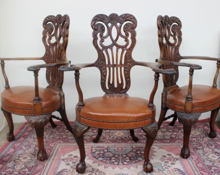 Sold for £820. A set of three 19th century mahogany elbow chairs, with a C scrolling and leaf carved pierced back, out scrolling arms with carved eagle terminals above a pad upholstered seat on leaf carved cabriole legs and claw and ball feet