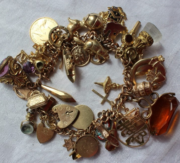 Sold for £650. A 9ct yellow gold charm bracelet set with numerous charms including a canoe, tankard, key, elephant, half sovereign, cruise liner, flat iron hardstone revolving fob seal etc overall approximately 85 grams