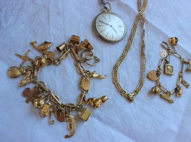 Sold for £590. A 9ct necklace with a central heart and rectangular links together with two 9ct charm bracelets set with numerous charms including a jug, piano, keys, gondola, boot, windmill etc, overall approximately 70 grams and a Trebex open faced pocket watch on a chain