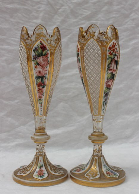 Sold for £580. A pair of Victorian overlaid glass vases, with opaque and clear glass painted with flowers and leaves, with gilt highlights, 23.5cm high