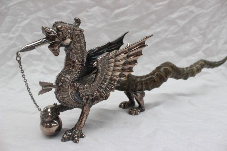 Sold for £1,420. A Welsh Dragon table lighter the silver plated body of the dragon finely formed with wick in mouth, a lighter in chest formed as an arrow, the large wings (one inscribed `YE DRAGON OF WANTLEY`) sweeping back over long twisted horn tail, raised on four silver plated feet overall length 54cm long x 16.5cm high