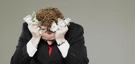 Mature-businessman-holding-scrunched-money