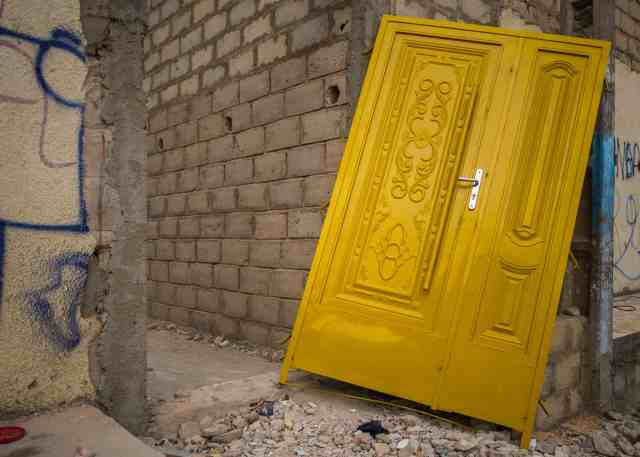 Brand new yellow door in the doorway of a concrete block house