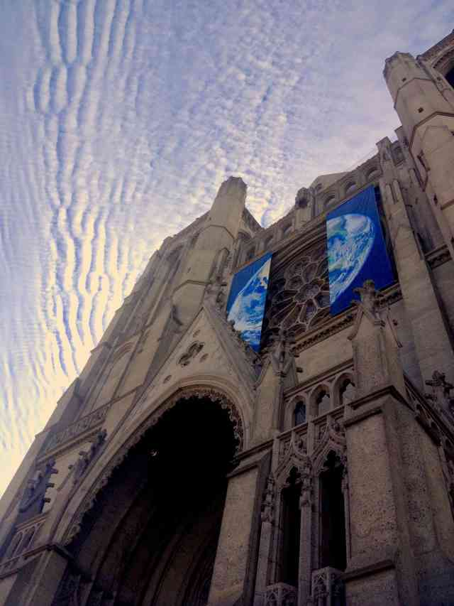 Image looking up at a cathedral with the two halves of a globe hanging on either side of the rose window. Blue sky with ripples of clouds