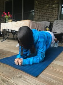 A person with long hair is planking on a yoga mat.