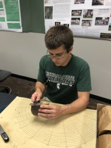 Jeff Painter in an archaeology lab studying ancient pottery