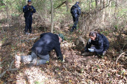 Dr. Isaac and Dr. Cornelison on a forensic case searching the forest floor