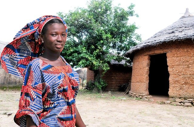African woman wearing traditional clothing and standing in front of a hut.