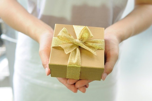 two hands holding a gift wrapped in gold paper with a gold bow