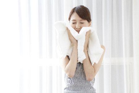 タイルでゴシゴシ顔を拭いている女性の写真