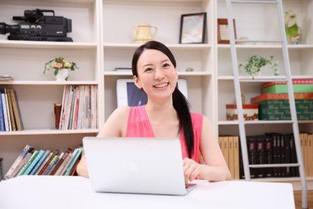 パソコンでYoutubeの動画を見て笑っている女性