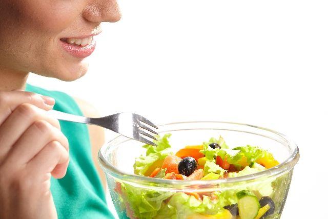 野菜のサラダだけで栄養不足の食事をする女性の写真