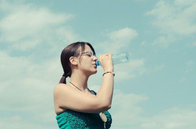水分不足を水を飲んで補う女性の写真