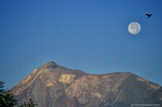 © The Moon and Fuego volcano at sunrise from the bedroom window, Antigua Guatemala by Rudy Giron