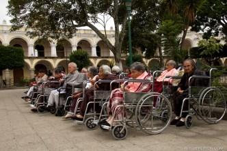 © Elderly on Wheelchairs Sunbathing at Park by Rudy Giron