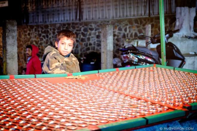 Rudy Giron: Antigua Guatemala &emdash; Boy Tending a Game Stand at the Town Fair in color