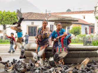 Mayan girls feed pigeons around a fountain in Parque Central in Antigua Guatemala by Rudy Giron