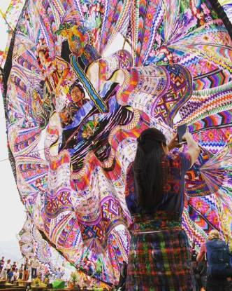 A Mayan woman records a video of the raising the 17-meter giant kite with the theme: «Identidad», Identity by Rudy Giron