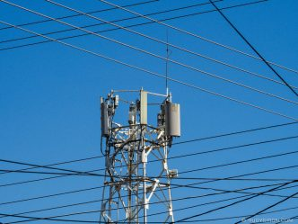 PHOTO STOCK: Cellular tower and wires against a blue sky