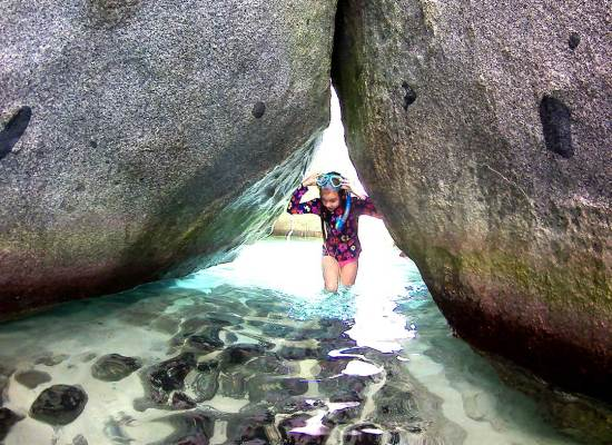 little girl in exploreing the shallow pools inside the Baths on Virgin Gorda