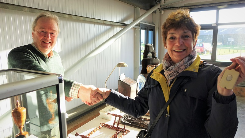 A customer buys an antique item at the Newark Antiques Fair