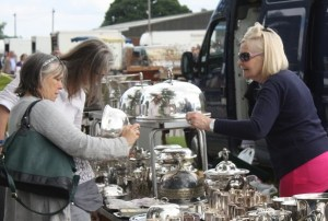 A visitor to an antiques fair buying some silver