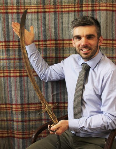 Auctioneer Aaron Dean with the antique sword which sold for £5,200
