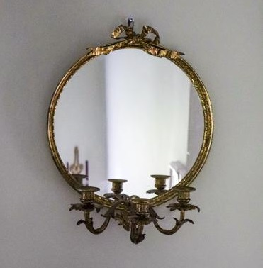 A 1950s round gilt framed girandole mirror from Janey Cave Antiques