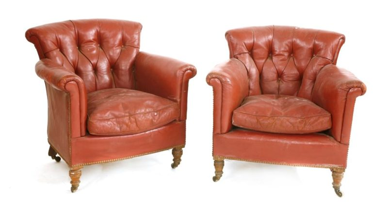A pair of antique Victorian crimson leather armchairs