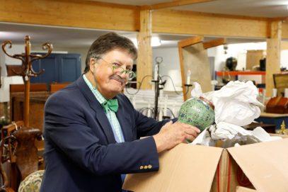 Tim Wonnacott unpacking items for sale in auction room