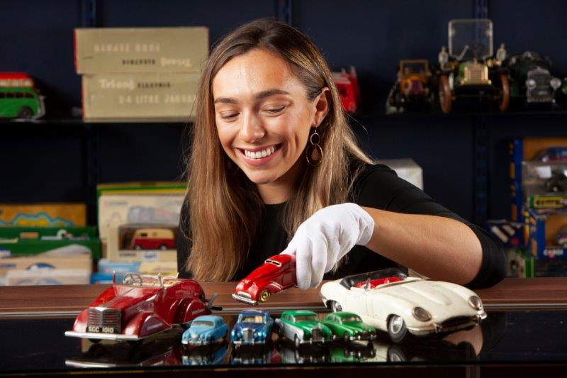 Hannah Murphy from McTear's examines a red EC01 Wonder Car model racing car which could fetch £250 at auction