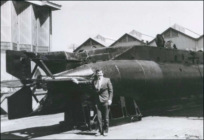Edmund 'Eddie' Goddard standing beside a mini submarine