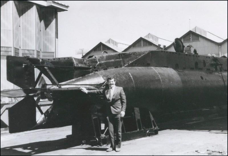Edmund 'Eddie' Goddard standing beside a mini submarine