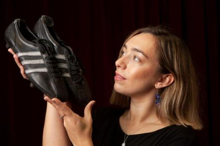 Hannah Murphy from McTear's with Celtic legend Tommy Gemmell's match worn boots from the 1967 European Cup Final which will go to auction on 19th July