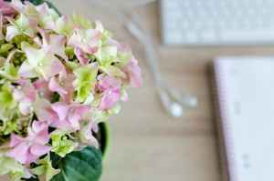 flower centerpiece beside book and computer keyboard on table