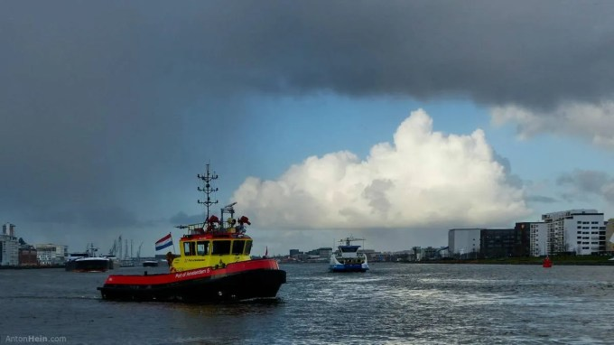 Rain and sunlit clouds over Amsterdam's IJ river