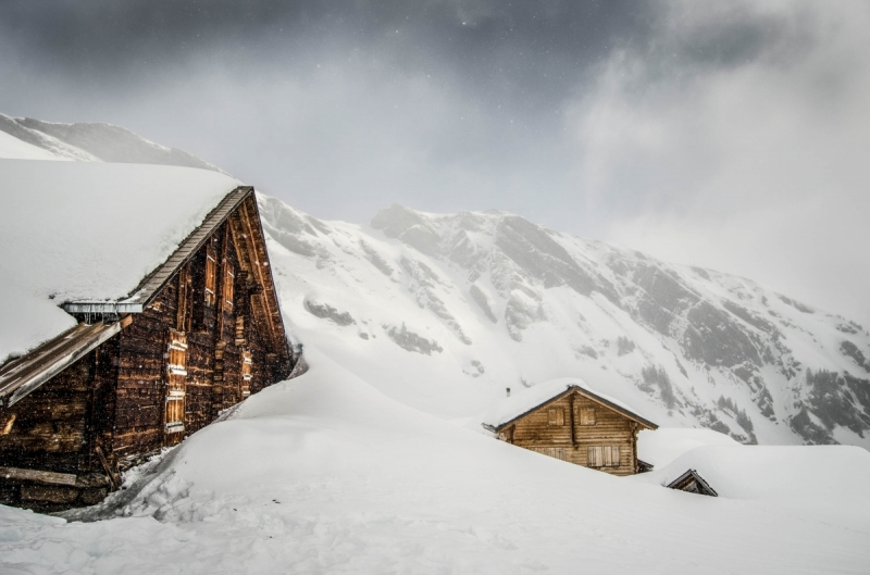Wooden Cottage in Swiss mountains with winter landscape