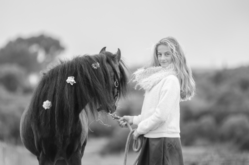 Girl and black pony stallion looking back