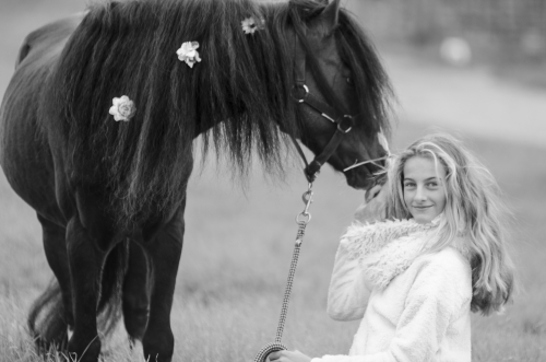Girl looking back and black pony stallion with flowers in mane