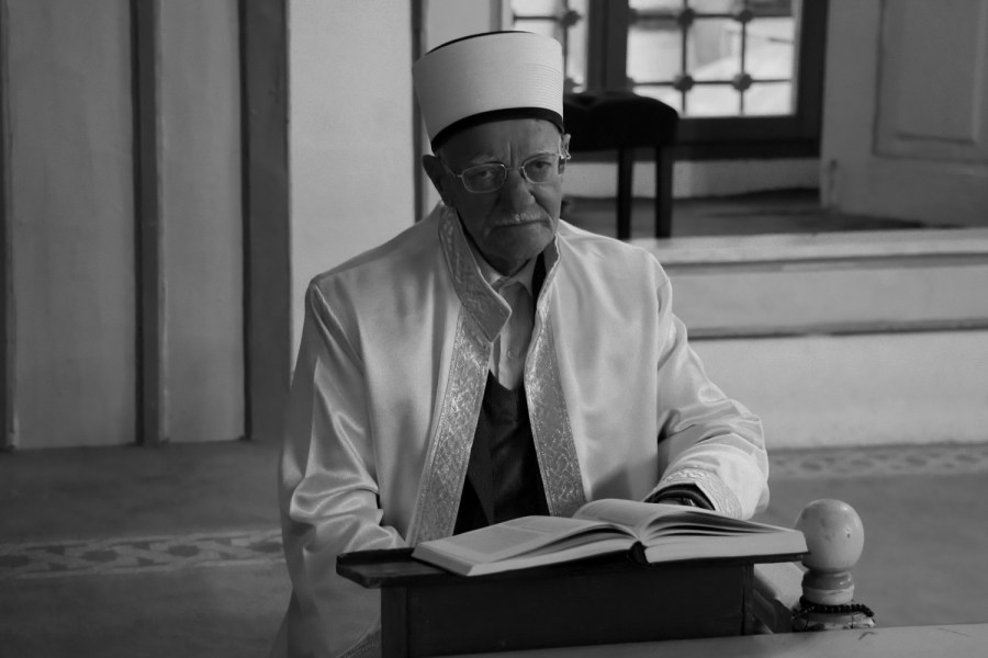 Cheikh assis devant un Coran