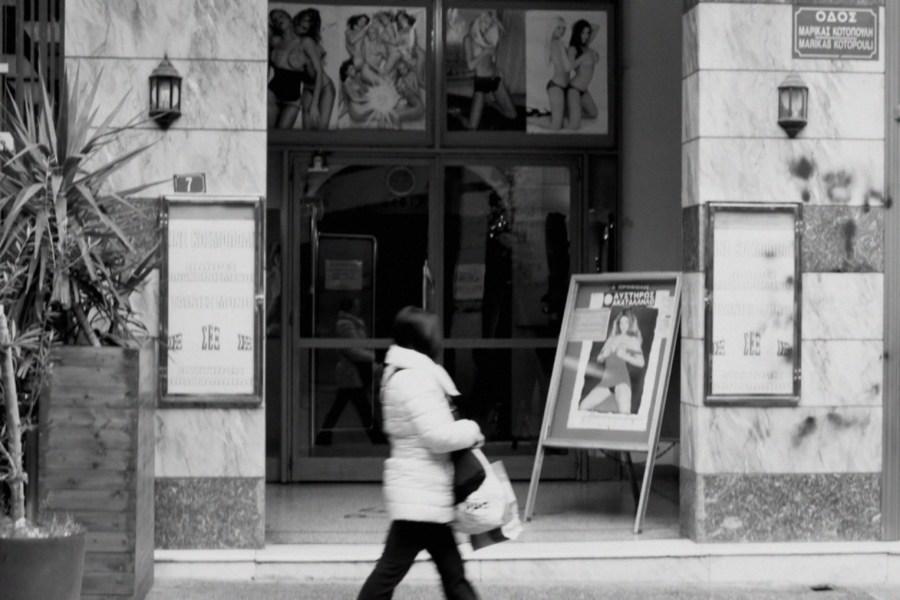 Une femme passe devant un théâtre / showroom X avec des affiches de scènes lesbiennes hardcore.