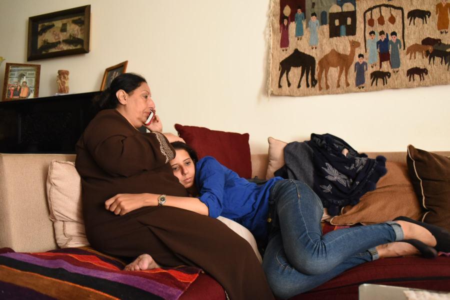 Une mère et sa fille en câlin sur un canapé