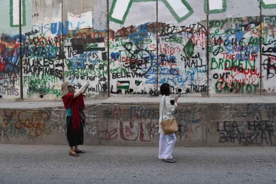 Touristes asiatiques photographiant le mur de séparation entre Israël et les Territoires palestiniens