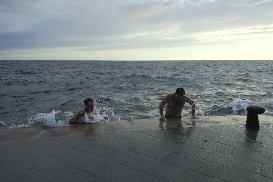 DEux nageurs s'extirpent d'une mer agitée en se hissant sur la digue du port